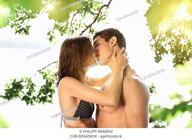 Young couple kissing at lakeside