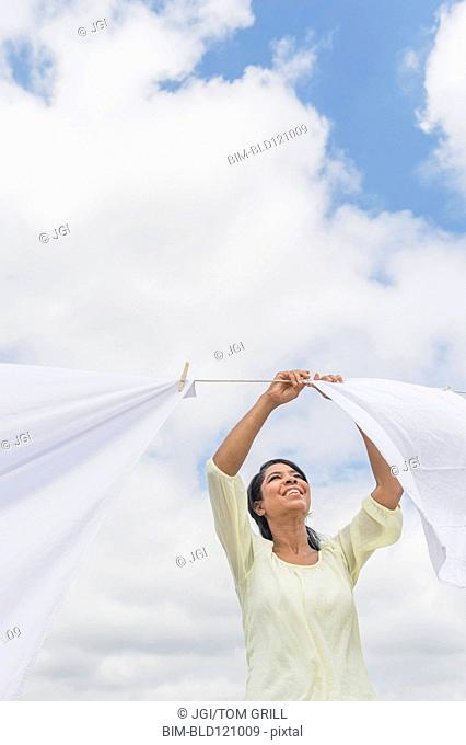 Black woman hanging sheets from clothesline