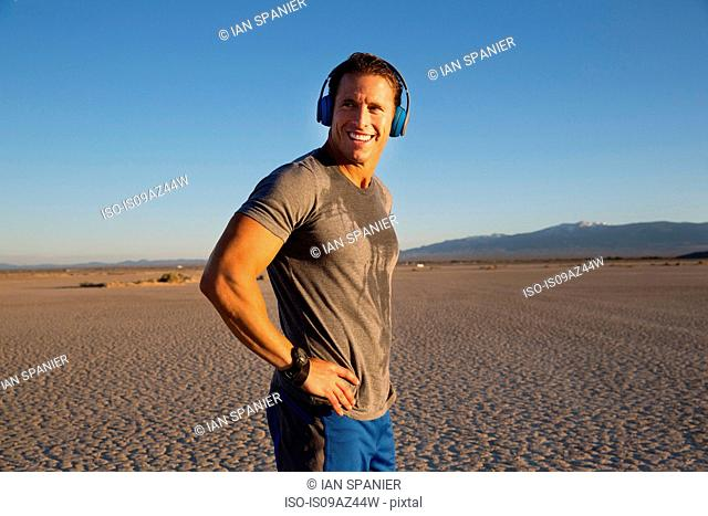 Man training, listening to headphone music on dry lake bed, El Mirage, California, USA