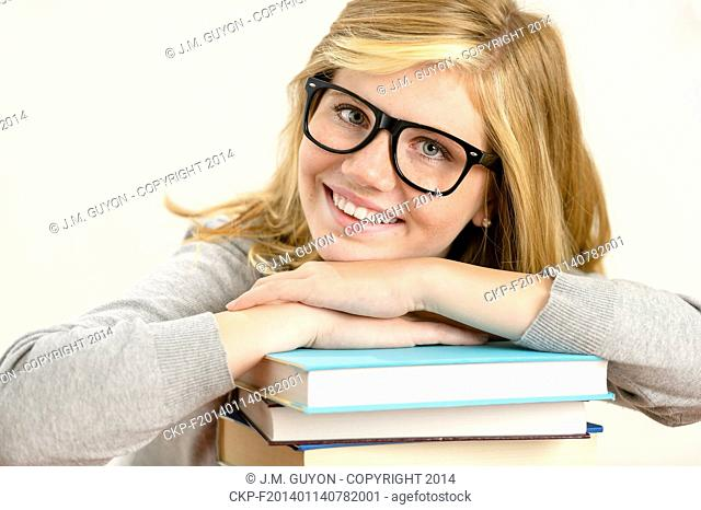 Happy girl student with stack of books smiling on white