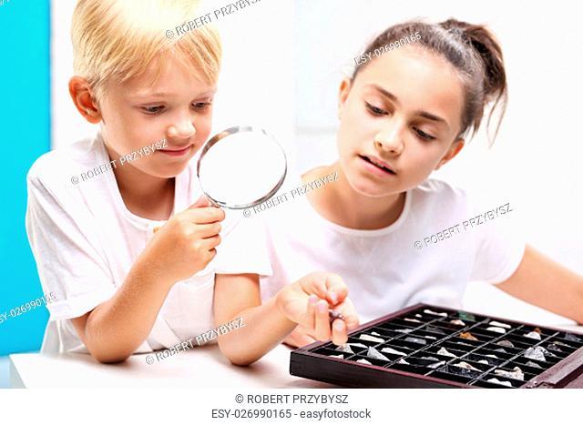 Geografia w szkole. Dzieci ogladaja mineraly pod lupa