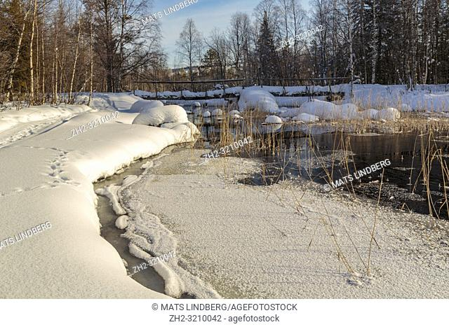 Creek in spring season with open water and snow and ice, wooden bridge and reed in the water, Boden county, Norrbotten, Sweden