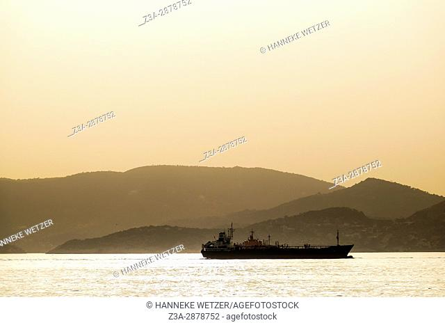 A ship in the sea passing by islands, Greece, Europe