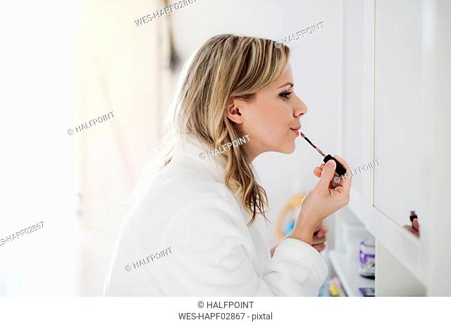 Woman in bathrobe applying make-up in the morning at home