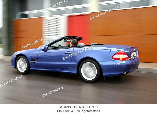 Mercedes SL 500, model year 2005-, blue moving, diagonal from the back, rear view, side view, City, open top