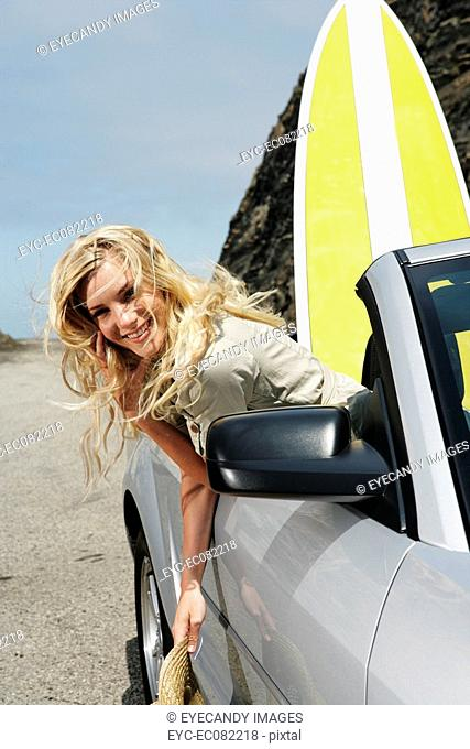 Portrait of happy young woman sitting in convertible with surfboard