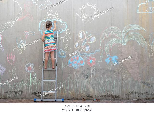 Girl standing on ladder drawing colourful pictures with chalk on a concrete wall