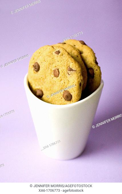 Freshly baked chocolate chip cookies in a white cup against a lavender background