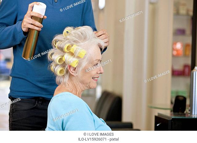 A male hairdresser applying hairspray to a female clients hair, close up
