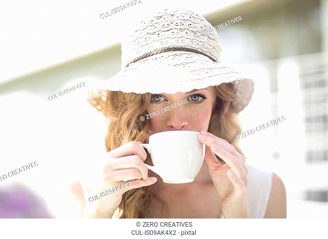 Portrait of young woman drinking from coffee cup at sidewalk cafe
