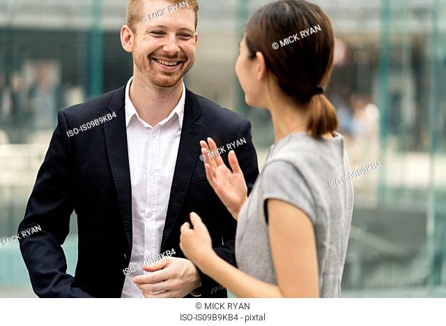 Young city businessman and woman having discussion outdoors