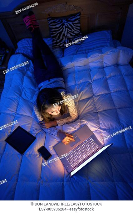 Teenage girl lying on a bed at night working on a laptop computer