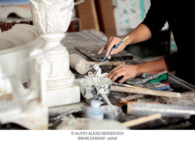 Caucasian artist sculpting with tool