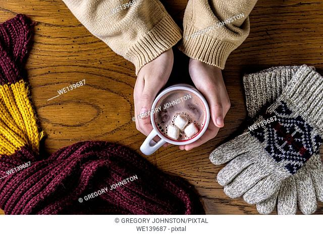 Overview shot of hands holding a hot cup of cocoa by gloves and a scarf