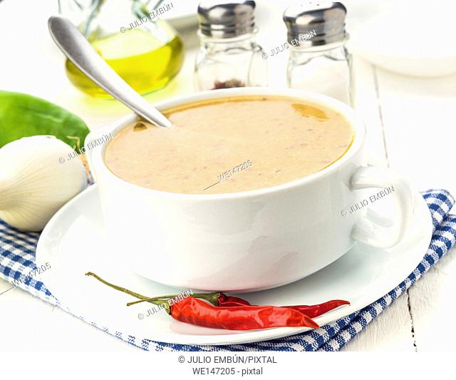 spicy vegetable soup with chili, on white wooden board