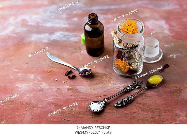 Blossoms of medical plants, medicine flasks, marigold salve and globules