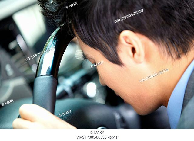 Asian Businessman Leaning Head At Starring Wheel