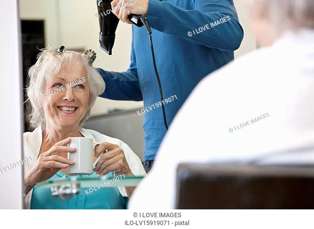 A senior woman drinking a hot beverage whilst having her hair dried