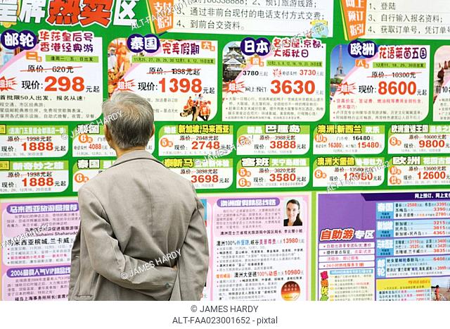 Man looking at ads on wall in Chinese, rear view