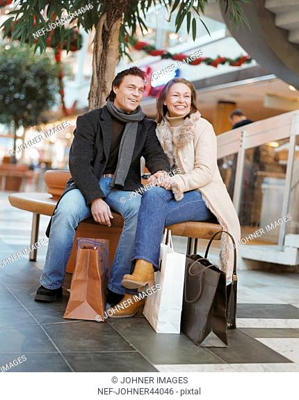Man and woman sitting on the bench in the mall and laughs