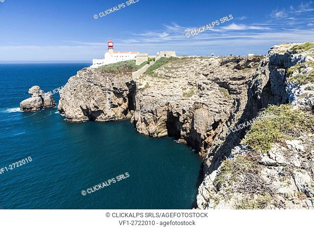 The cliffs and lighthouse overlooks the blue Atlantic ocean at Cabo De San Vicente Sagres Algarve Portugal Europe