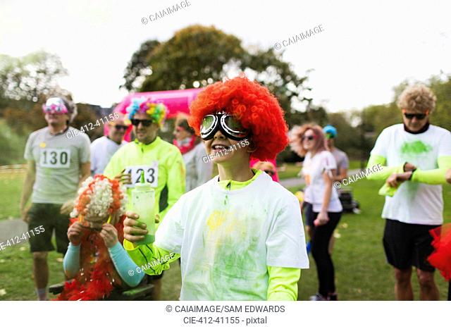 Playful boy runner in wig covered in holi powder at charity run in park
