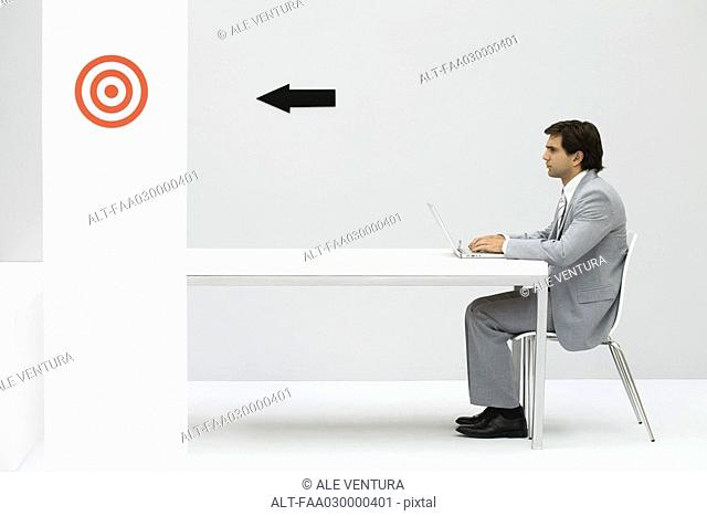 Man sitting at desk, using laptop computer, arrow on wall pointing at bullseye