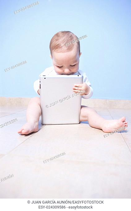 Sitting baby boy discovering a tablet pc