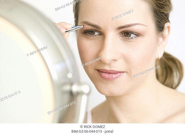 Hungarian woman tweezing eyebrows