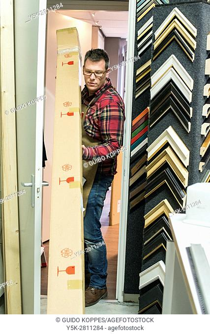 Goirle, Netherlands. Mid adult male craftsman and picture framemaker, recieving some new materials for picture frame production