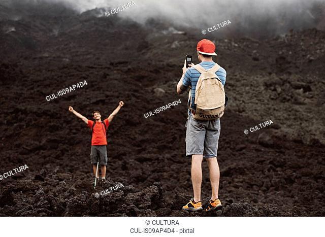 Young man photographing friend at Pacaya volcano, Antigua, Guatemala
