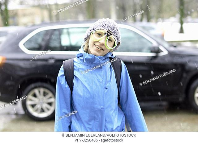 woman with funny eyeglasses standing in winter at street, snowing, in Munich, Germany