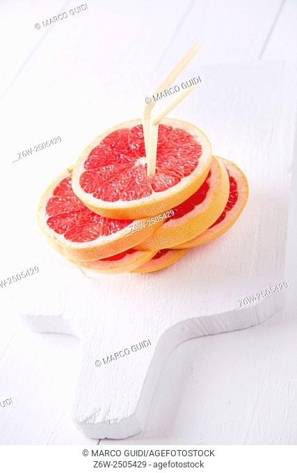 Aperitif with slices of red grapefruit on white-border