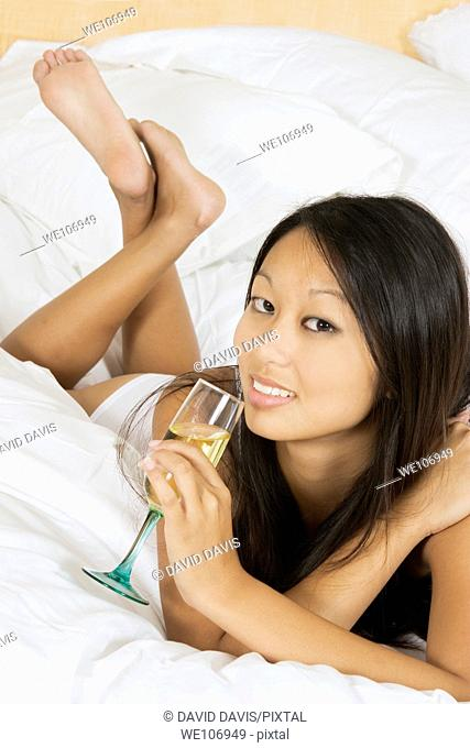 Asian woman in early 20's laying in bed with a glass of white wine