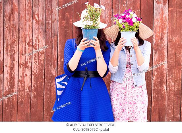Two females wearing sun hats, holding potted plants in front of their faces