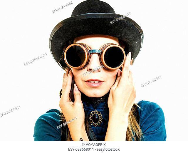 Young steampunk islolated girl on white wearing fancy hat. Fantasy old fashion with stylish topper and goggle