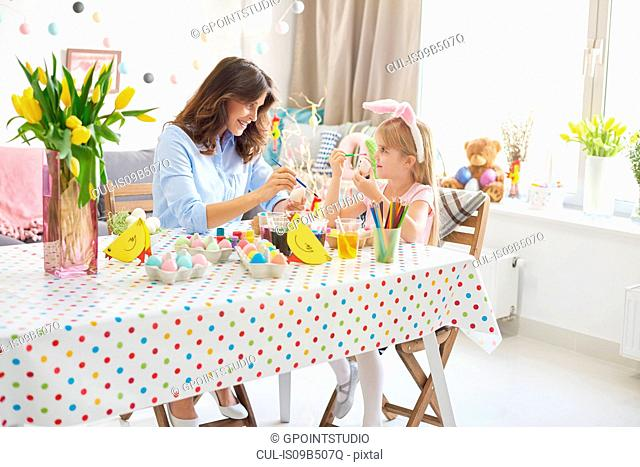 Girl and mother painting easter eggs at table