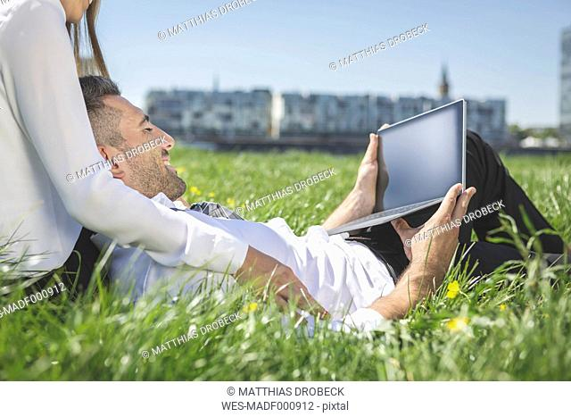 Business couple with digital tablet in meadow