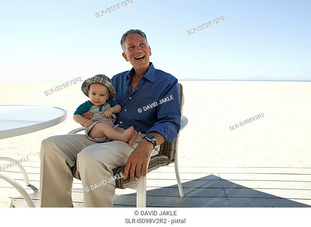 Grandfather sitting with baby grandson
