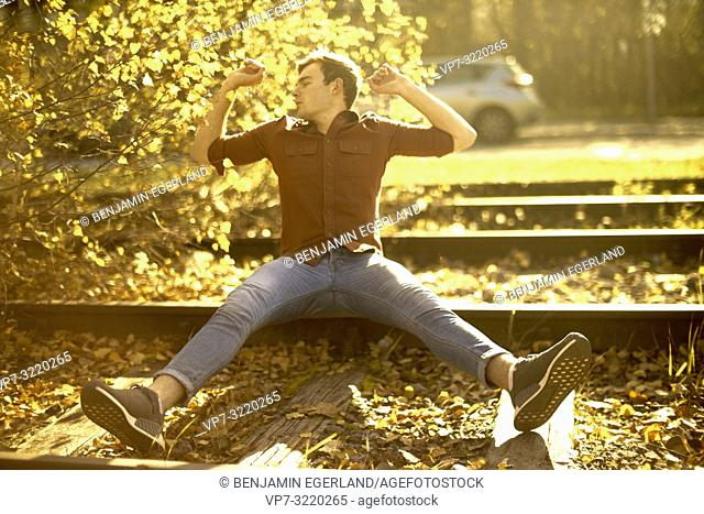 Young man stretching arms outdoors sitting on rails autumn in city, freedom, tired, joy, relaxing, chilling, Munich, Germany