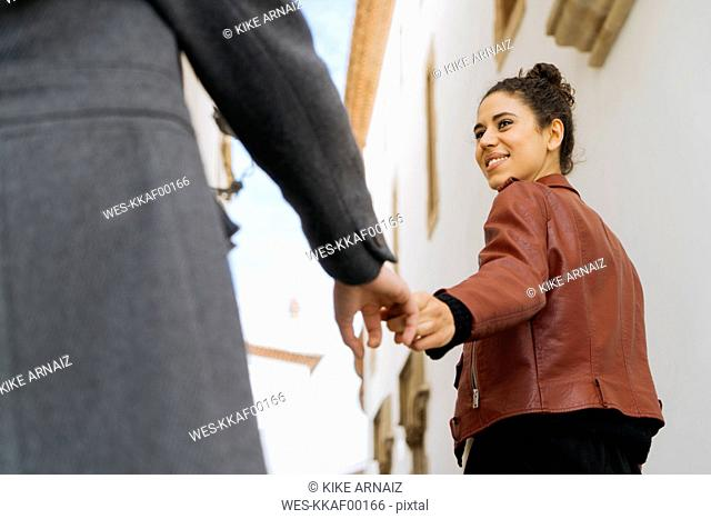 Portrait of smiling young woman holding hand with her friend