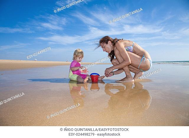 summer family of two years blonde baby pink and yellow swimsuit sitting on water with brunette woman mother in bikini with red plastic bucket at sea shore beach...