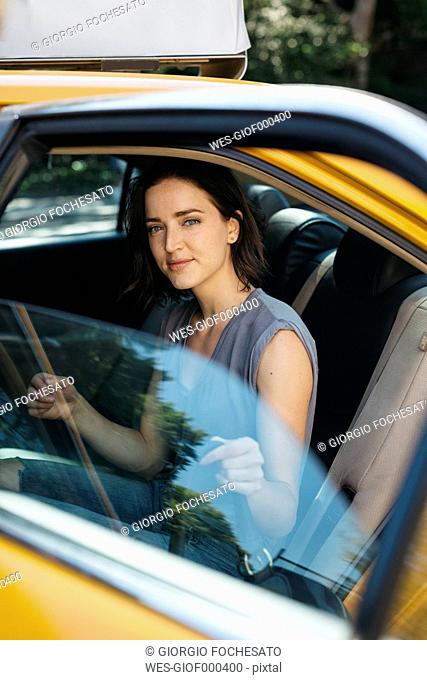 USA, New York City, portrait of smiling young woman getting on a yellow cab