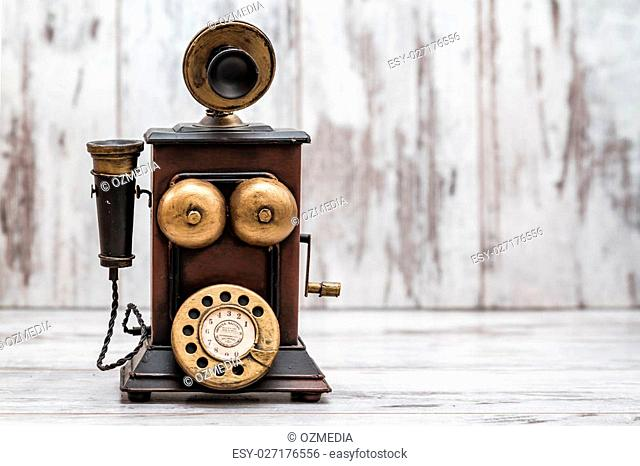Retro phone as home decoration on white wooden background