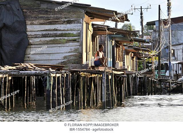 Woman in front of her humble wooden house, stilt house in the mangrove area in the estuary of the Rio Anchicaya river in the Pacific at high tide, Bajamar slum