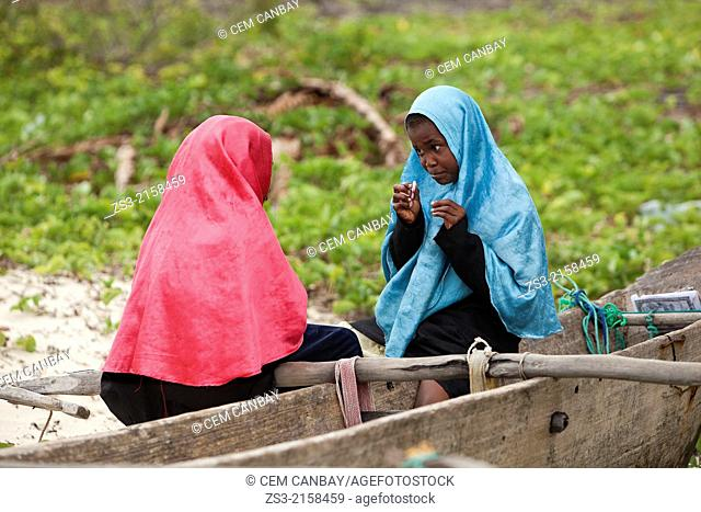 Muslim girls sitting on a boat at the beach, Jambiani, Zanzibar Island, Tanzania, Indian Ocean, East Africa