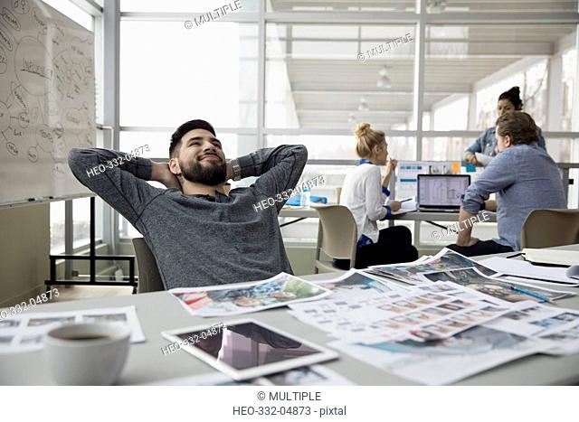 Confident creative male designer with hands behind head in office