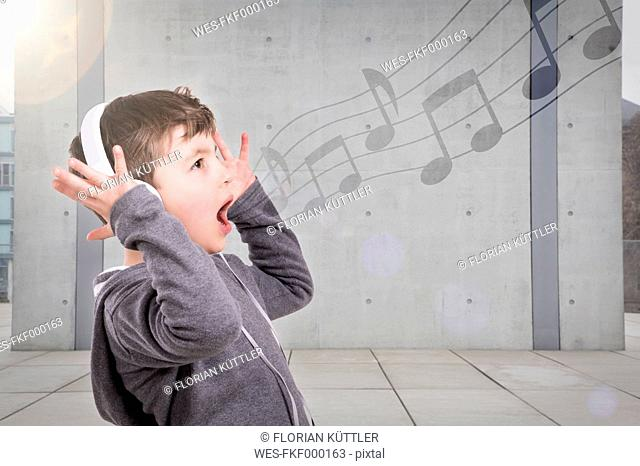 Germany, Brandenburg, Boy listening music with head phones