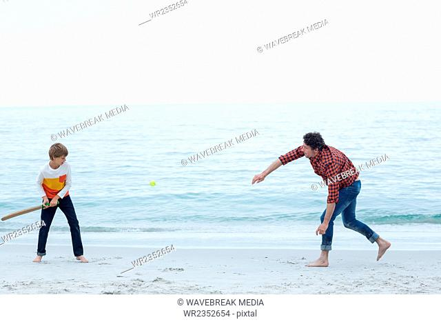 Father and son playing cricket at sea shore