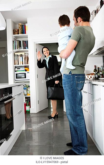 A mother leaving for work, waving goodbye to her partner and baby son